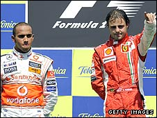 Felipe Massa celebrates on the podium as Lewis Hamilton rues second place