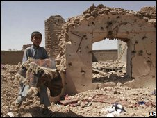 A boy stands next to the rubble of his house, following the US air strike in western Afghanistan