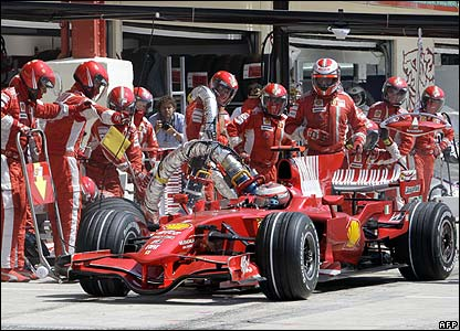 Kimi Raikkonen pulls away from his second pit stop with the refuelling hose still attached