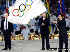 Beijing mayor Guo Jinlong, with the IOC's Jacques Rogge, hands the Olympic flag to London mayor Boris Johnson