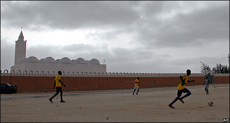 Boys play football in front of mosque