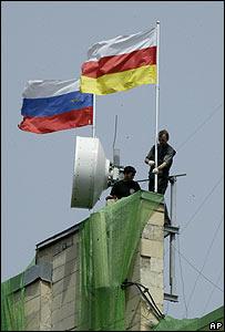 Dos empleados municipales enarbolan en un edificio público de Tsjinvali, capital de Osetia del Sur, una bandera rusa (izq.) y otra de la provincia separatista