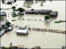 Residents wade through flood waters in Saharsa village near  Kosi river in Bihar on 25 August