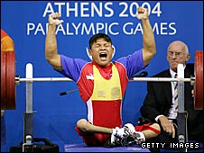 Thailand's Thongsa Marasri celebrates lifting 165kg to win silver in the men's 48kg class