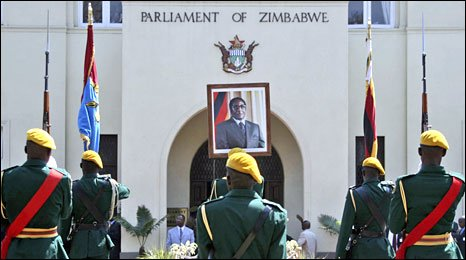 Robert Mugabe's picture hangs at the entrance of the parliament building as a guard of honour stand during the opening ceremony in Harare, 26 August 2008