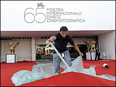 A worker prepares the red carpet at the entrance of the cinema palace