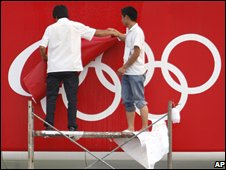 Workers dismantle the five-ring Olympic emblem
