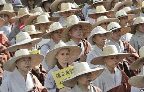 Monks in straw hats form disciplined ranks in the mass protest