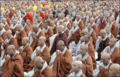 Brown and gray-robed monks bow heads in prayer at large protests
