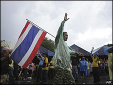 A protester waves a Thai flag in the compound of Government House in Bangkok