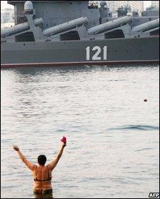 A bather on Sevastopol city beach welcomes Russian missile cruiser Moskva as it entering Sevastopol bay