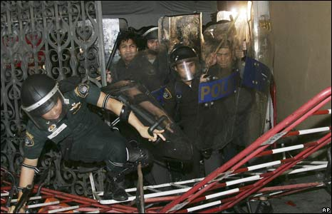 Thai riot police break into the Government House through a gate in Bangkok, Thailand, early Wednesday August 27, 2008.