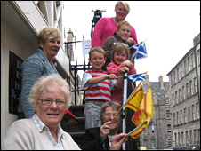 Rita Nicol and other well-wishers wave their flags during the parade