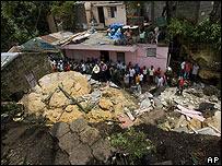 Residentes contemplan varias propiedades destruidas por un alud desatado por la lluvias en Guachupita, Santo Domingo
