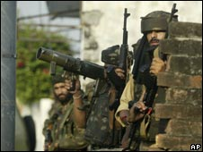 Indian soldiers take position near a building where suspected militants were hiding near Jammu on 27 August