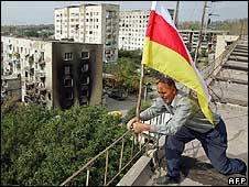 A man raises a South Ossetia flag on the roof of a building in South Ossetia (27/08/08)