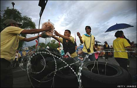 Demonstrators pass food over the barricades around Government House in Bangkok on Thursday