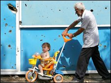 A man pushes a child through damaged Tskhinvali
