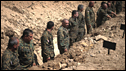 Georgian soldiers stand in a mass grave dug for unknown Georgian troops killed during the conflict