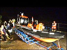 The stricken lifeboat being towed ashore