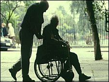 Carer pushing person in wheelchair