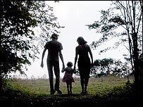 A man and a woman walking with a child