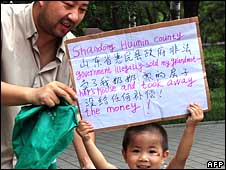 "Hai Mingyu and his son, who were chased out of one of Beijing's protest parks. The sign reads: ""Shandong Huimin county government illegally sold my grandmother""s house and took away the money!"""