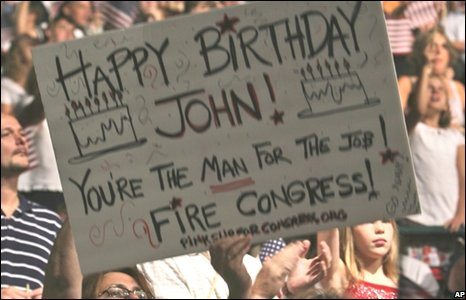 Supporters hold a placard with a happy birthday message for John McCain