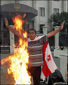 A man burns a Russian flag outside the Russian embassy in Tbilisi on 27 August