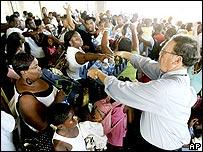 Un hombre entrega botellas de agua a los evacuados en un refugio de Louisiana