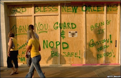 Tourists walk past a boarded-up bar in New Orleans on 30 August.