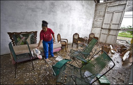 Woman inspects the remnants of her furniture
