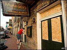 A worker boards up a business on Bourbon Street, New Orleans