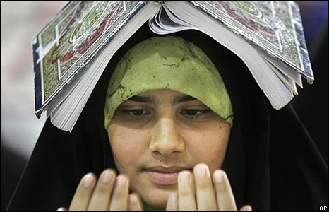 Iraq woman in Najaf rests her Koran on her head to free both hands for praying