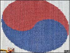South Korean workmen create a giant national flag on a Seoul government building