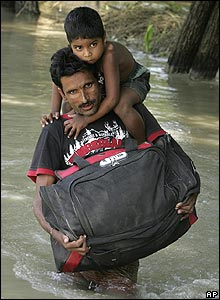 Father carries his boy through flood waters in Bihar