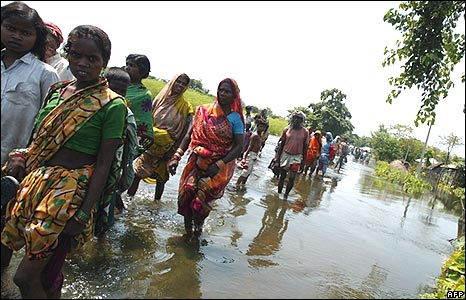 Families wade through flood waters in Gopalganj, Poornia district