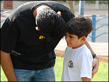Adir Danino, 7, is reassured by his father, Michel