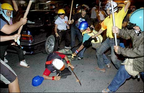 Anti-government protesters fight a pro-government supporter (centre) in Bangkok