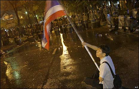 A Thai pro-government protestor waves a national flag in front of riot police in Bangkok