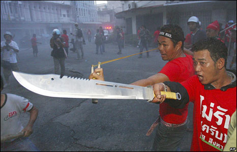 Pro-government supporters wield a sling and a knife near the government compound