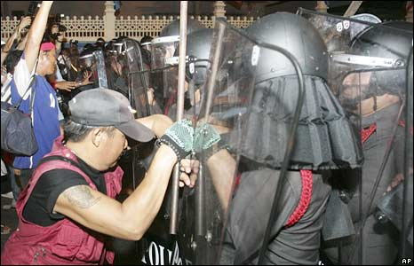 Pro-government supporters try to push through a  riot police cordon in Bangkok