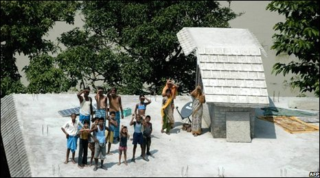 Stranded villagers wait on a roof for help