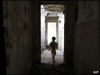 Мальчик в поврежденном во время конфликта доме в Цхинвали (снимок 1 сентября 2008)