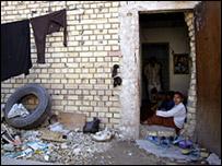فتاة تجلس أمام منزلها في بغداد