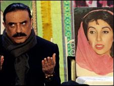 Asif Zardari beside a picture of his former wife Benazir Bhutto