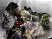 Mujer yace junto a su hijo que se recupera de su malnutrición.