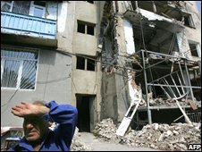 A South Ossetian man sits near a destroyed building in Tskhinvali