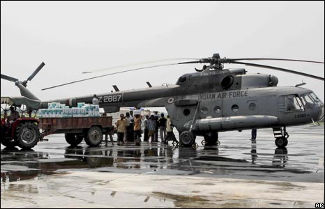 Workers load relief material onto an Indian air force chopper for distribution in flood-hit areas in Purnea district.