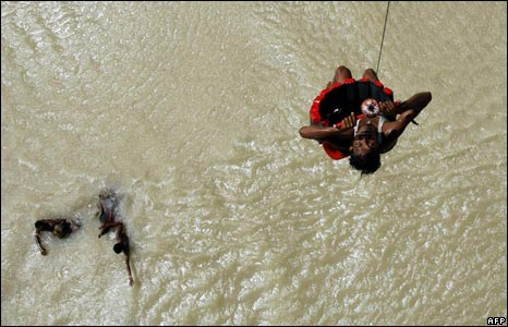 A man displaced by floods is winched to safety by an Indian air force helicopter in Chakramibasa village in Madhepura district.